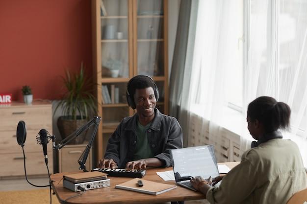 젊은 아프리카 계 미국인 부부의 높은 각도 초상화 함께 음악을 작곡 하 고 행복 하 게 웃 고 서로 찾고 공간을 복사