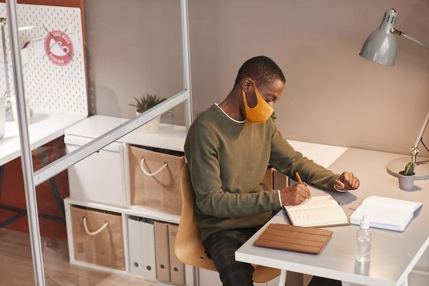 オフィスのキュービクル、コピースペースのデスクで作業中にマスクを着用し、プランナーで書いている若いアフリカ系アメリカ人男性の高角度の肖像画