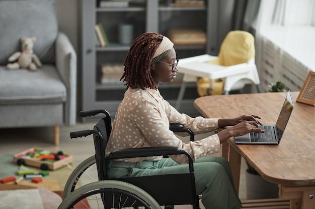 Высокий угол портрета молодой афро-американской женщины в инвалидной коляске во время работы из дома с детскими игрушками в фоновом режиме, копией пространства