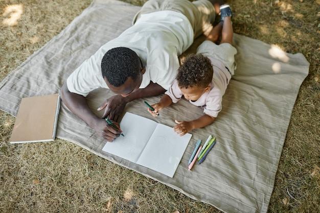 Портрет молодого афроамериканского отца под высоким углом, играющего с милым сыном в парке, лежа на гр ...