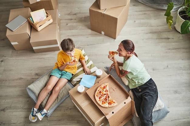 移動を祝いながら段ボール箱からピザを食べる若い母と息子のハイアングルの肖像画...
