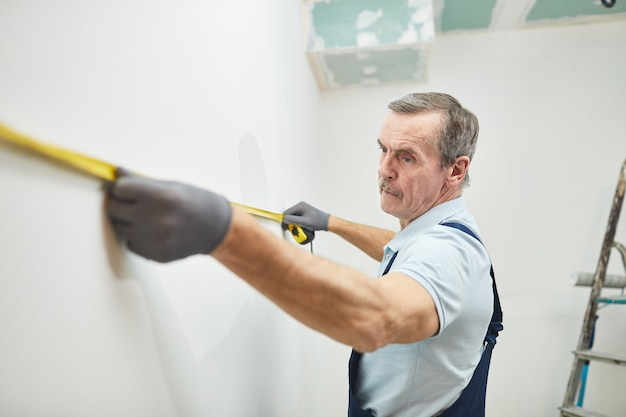 High angle portrait of senior construction worker measuring wall while renovating house, copy space