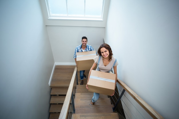 High angle portrait of smiling couple holding cardboard boxes while climbing steps