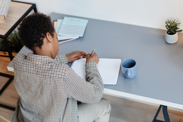 High angle portrait of teenage african-american boy doing homework at home, copy space
