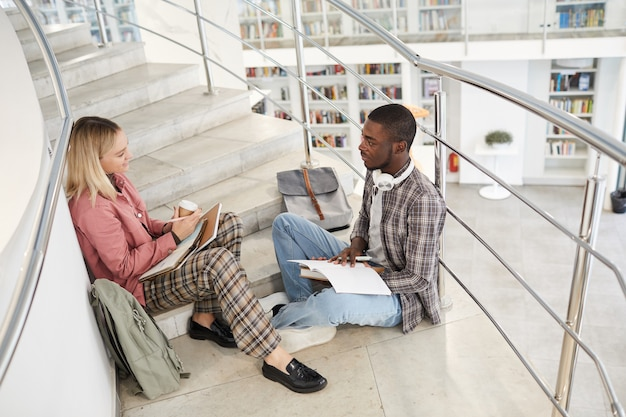 High angle portrait of two students chatting while sitting on stairs in college and working on homework,