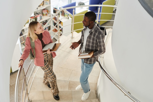High angle portrait of two students chatting while standing on spiral staircase in college and holding books,