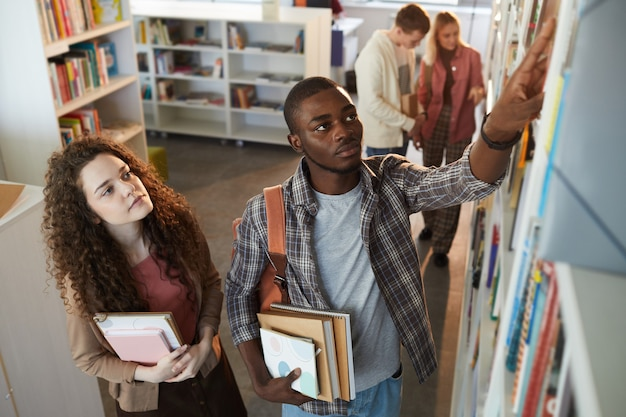 High angle portrait of two students taking books off shelf in school library,