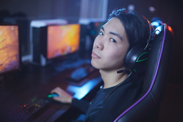High angle portrait of young asian man  playing video games in cyber sports chair, copy space
