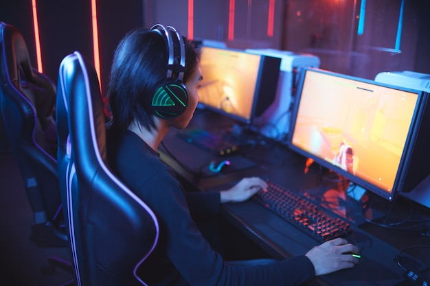 High angle portrait of young asian man playing video games and wearing headphones in dark cyber sport interior, copy space