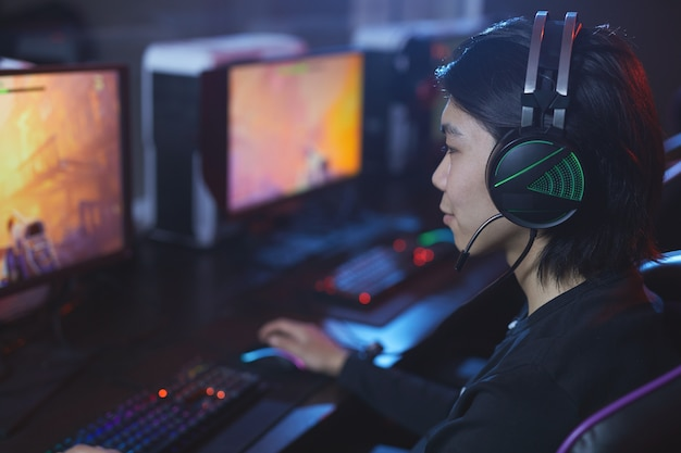 High angle portrait of young asian man playing videogames and wearing headphones in dark cyber interior, copy space