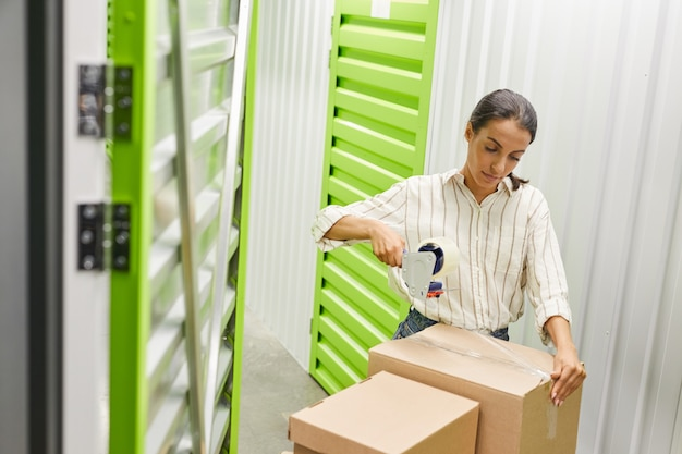 High angle portrait of young woman packing boxes with tape gun while standing by self storage unit, copy space