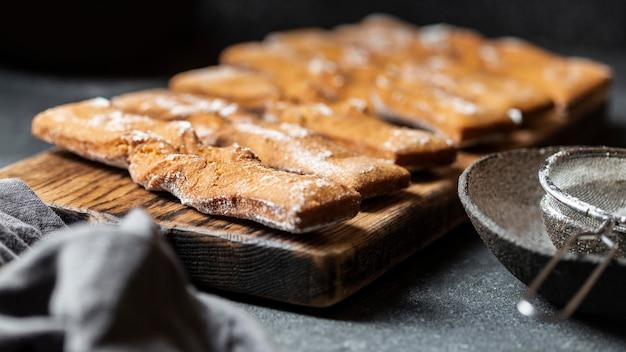 Alto angolo di dolci di zucchero a velo con setaccio