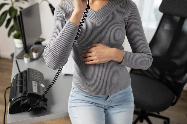 Alto angolo di imprenditrice incinta parlando al telefono in ufficio