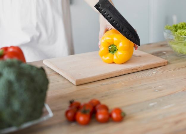High angle pregnant woman cutting pepper