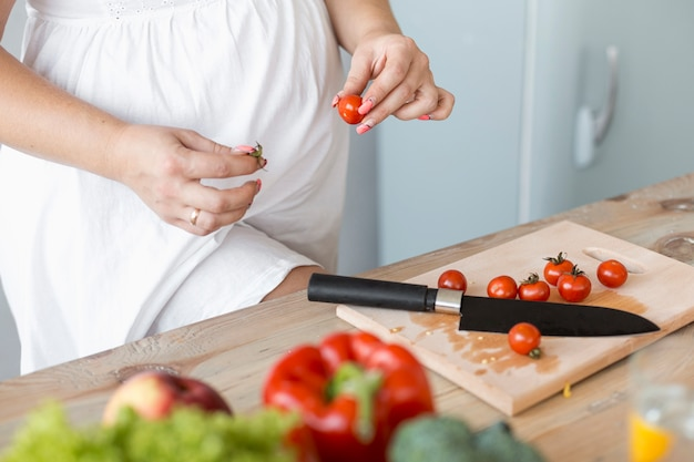 High angle pregnant woman cutting vegetables