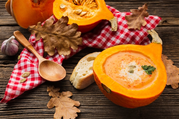 High angle pumpkin bisque and wooden spoon with ingredients and leaves