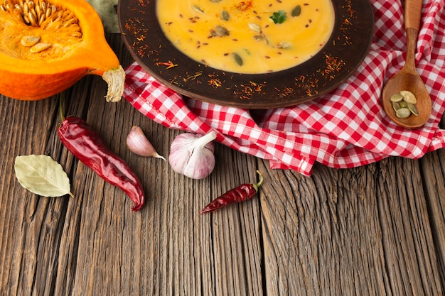 High angle pumpkin bisque and wooden spoon with ingredients