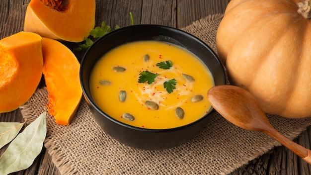 High angle pumpkin soup in bowl with pumpkin and wooden spoon