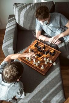 Ragazzi messi in quarantena ad alto angolo che giocano a scacchi