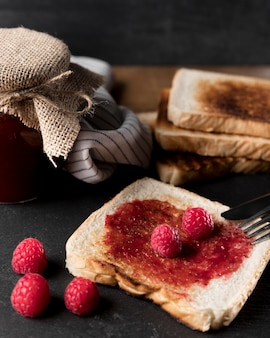 High angle of raspberry jam on bread with jar