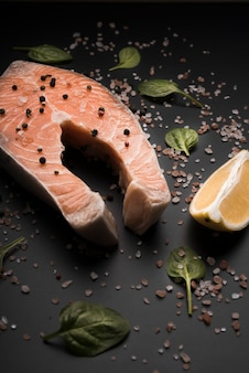 High angle raw salmon steak with pepper and lemon