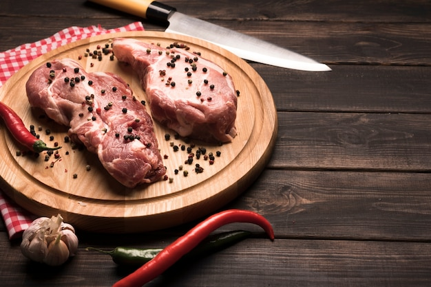 High angle raw steaks on wooden board with peppers
