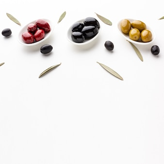 High angle red black yellow olives on plates