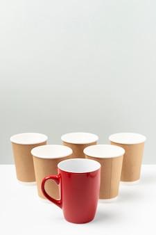 Tazza rossa ad alto angolo e bicchieri di carta