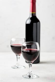 Vino rosso dell'angolo alto in vetri accanto alla bottiglia