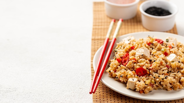 High angle rice with vegetables soy sauce and chopsticks with copy space