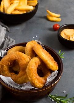Alto angolo di patatine fritte in una ciotola con le erbe