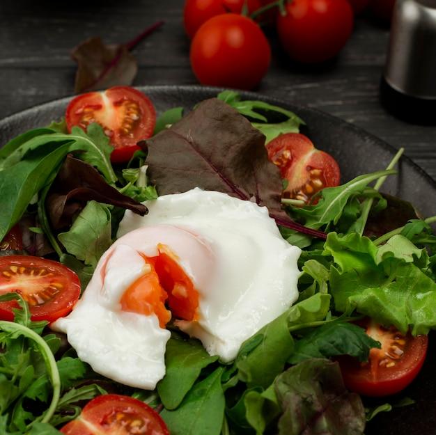 Insalata di angolo alto con uovo fritto e pomodori