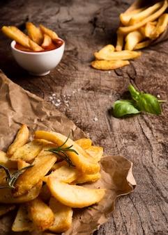 Alto angolo di patatine fritte salate con ketchup ed erbe aromatiche