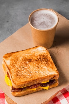 High angle sandwich with bacon and cheese with coffee
