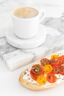 크림 치즈와 체리 토마토가 들어간 하이 앵글 샌드위치와 커피 컵