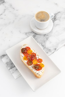 커피와 함께 접시에 크림 치즈와 토마토와 높은 각도 샌드위치