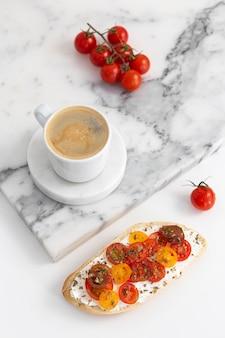 크림 치즈와 토마토 커피 컵과 함께 높은 각도 샌드위치