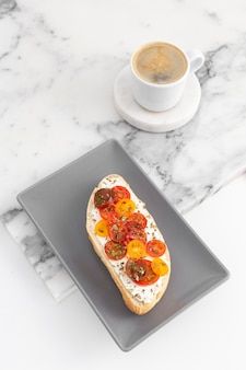 High angle sandwich with cream cheese and tomatoes with coffee