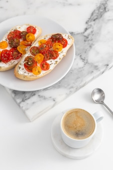 High angle sandwiches with cream cheese and tomatoes on plate with coffee