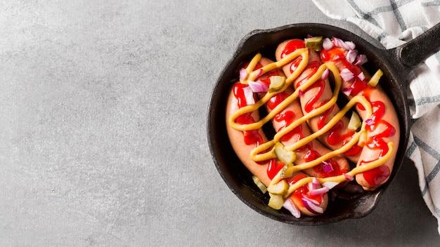 Сосиски и соусы под острым углом на сковороде с копировальным пространством