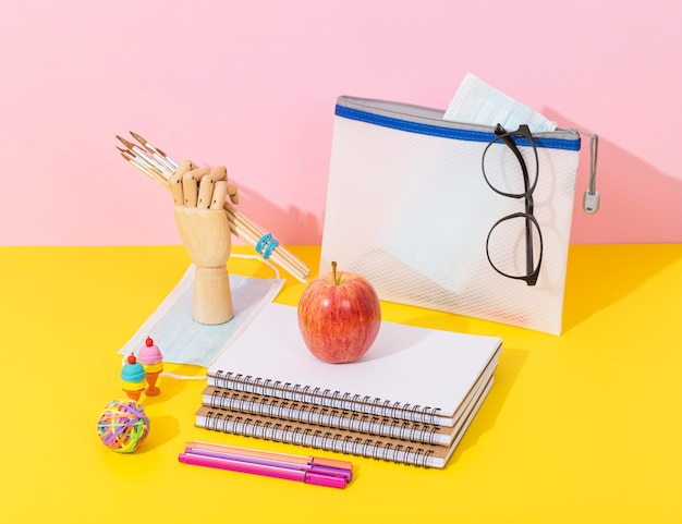 High angle of school supplies with notebooks and apple