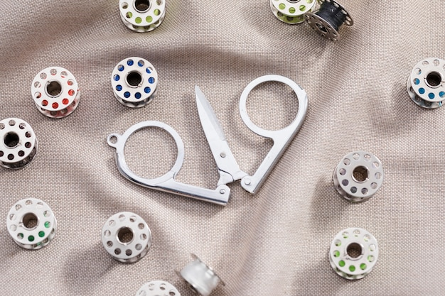 High angle of scissors on textile with sewing machine shuttles