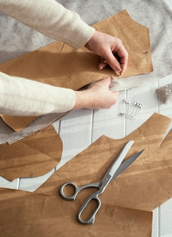 High angle of seamstress with fabrics and scissors