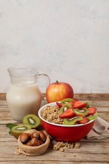 Alto angolo di selezione di cereali per la colazione in una ciotola con frutta e copia spazio