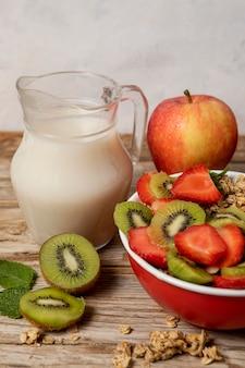 Alto angolo di selezione di cereali per la colazione in una ciotola con latte e frutta