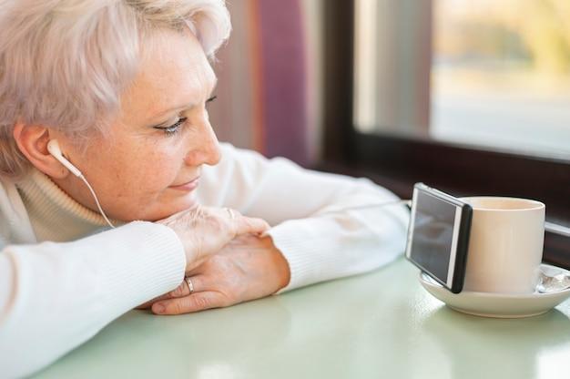 High angle senior female watching videos on phone