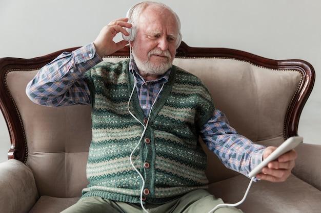 High angle senior playing music on phone