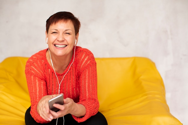 High angle senior woman listening music mock-up