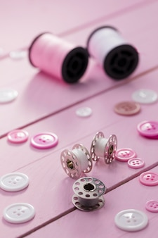 High angle of sewing machine shuttles with buttons and thread