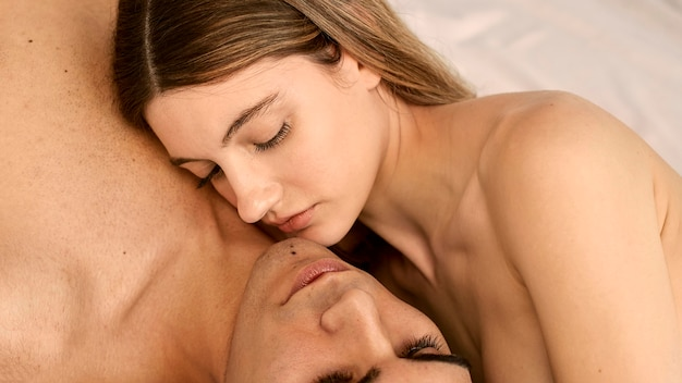 High angle of shirtless man and woman being intimate